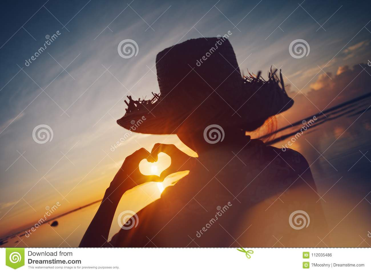 Woman In Straw Hat Making Heart Symbol With Her Hands At Sunrise