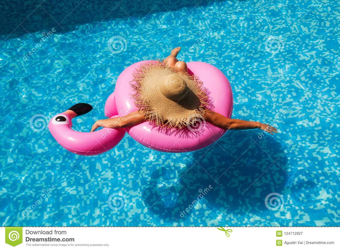 Woman with straw hat in the pool with an inflatable pink flamingo