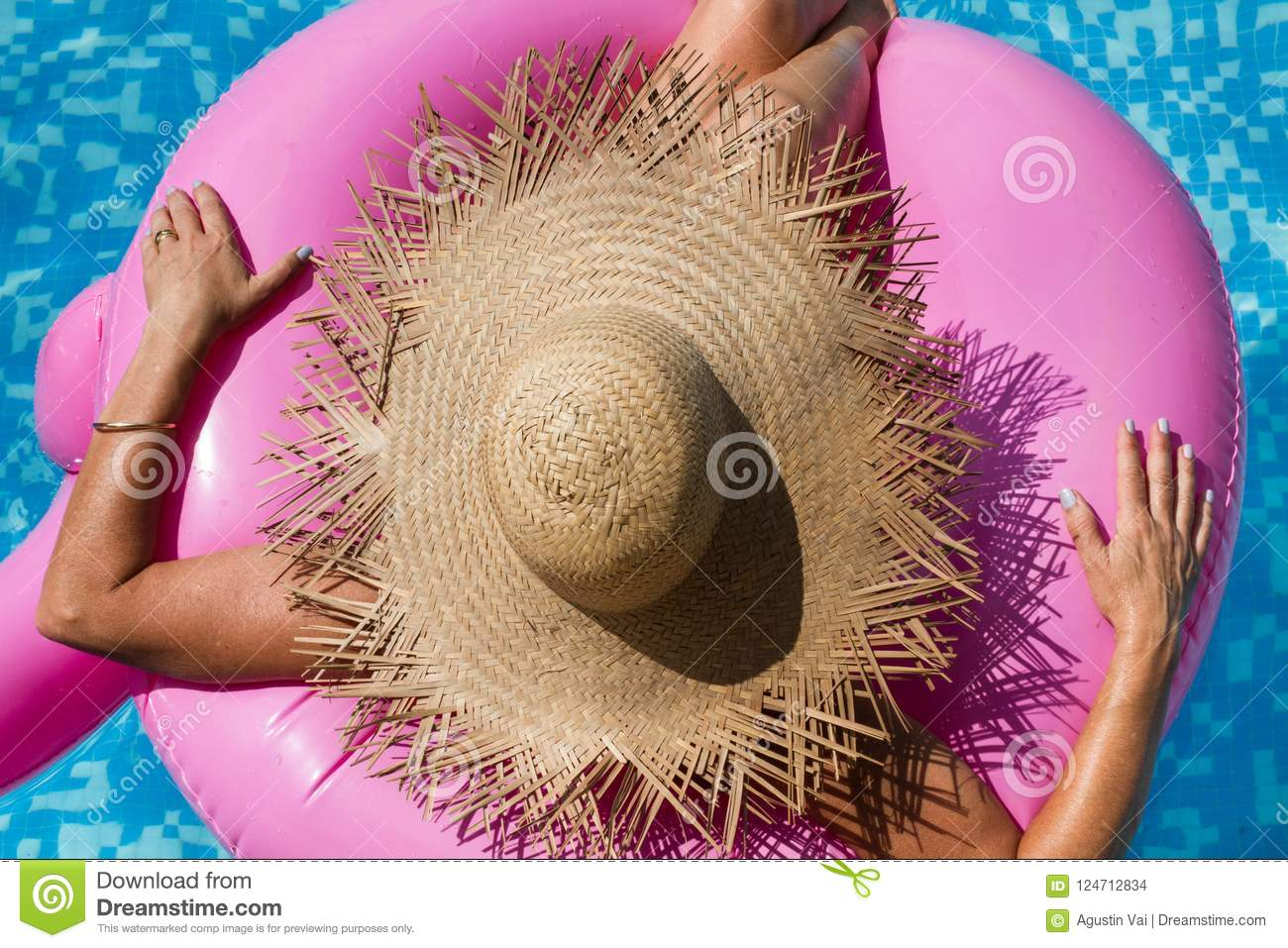 Woman with straw hat in the pool with an inflatable pink toy