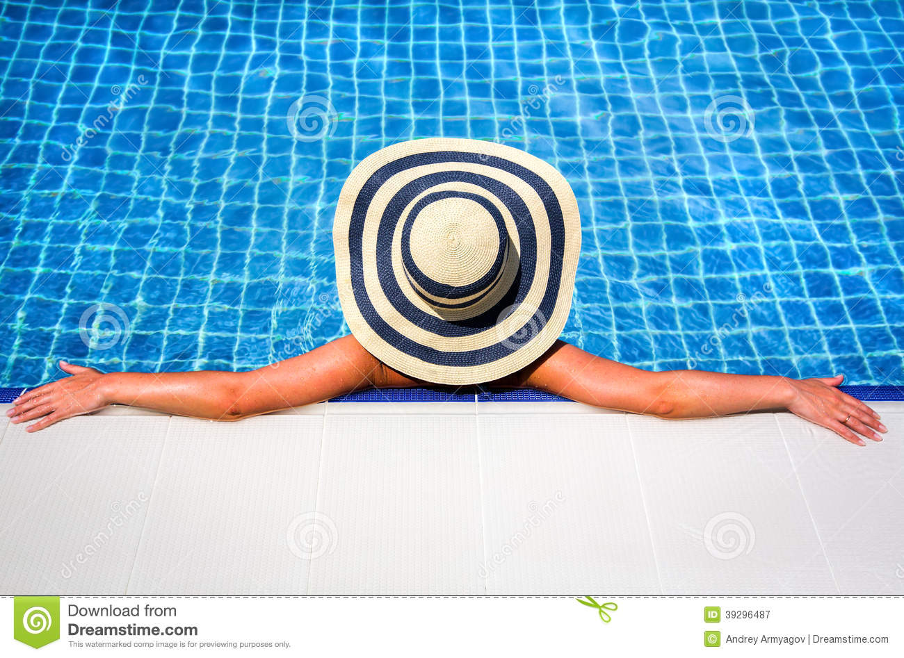 Woman in straw hat relaxing swimming pool