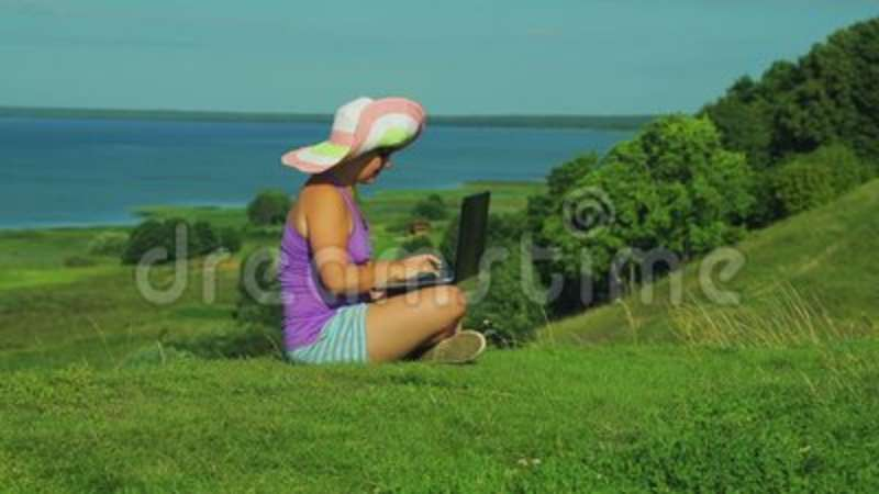 faaa586aab729 A woman in a straw hat sits on a mountain overlooking the lake and closes  the laptop lid.