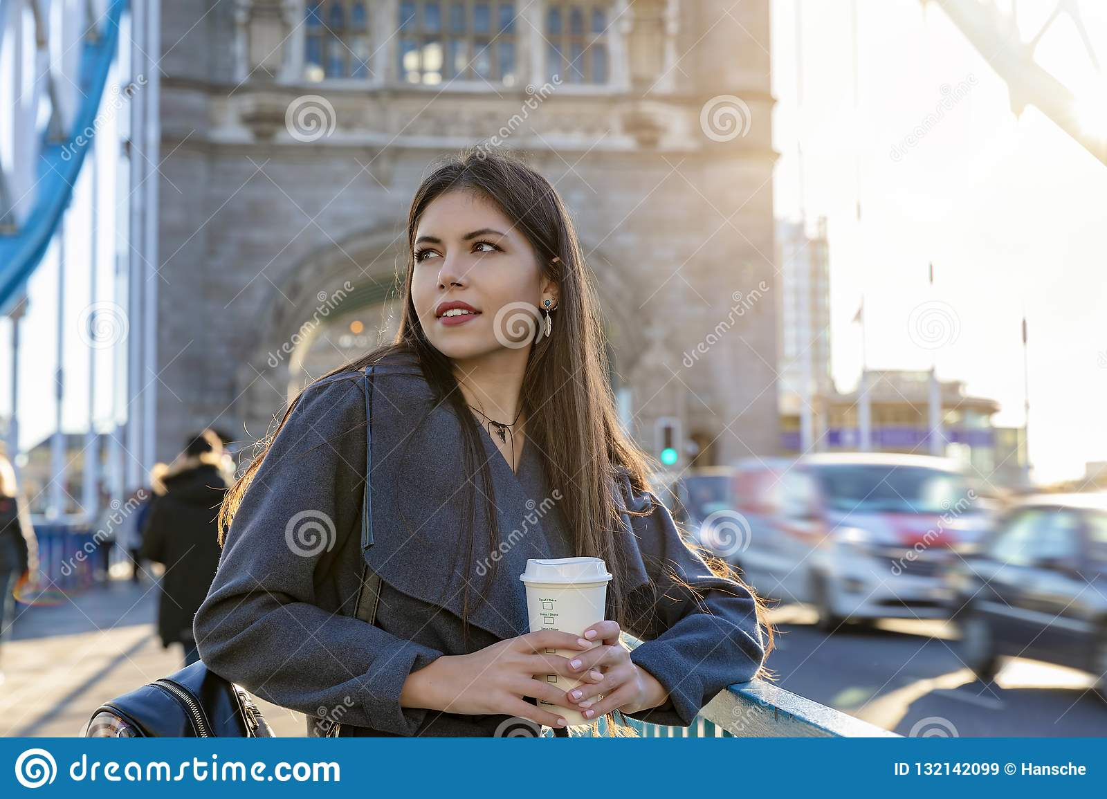 Woman on a street with a coffee in her hand, Tower Bridge, London, UK