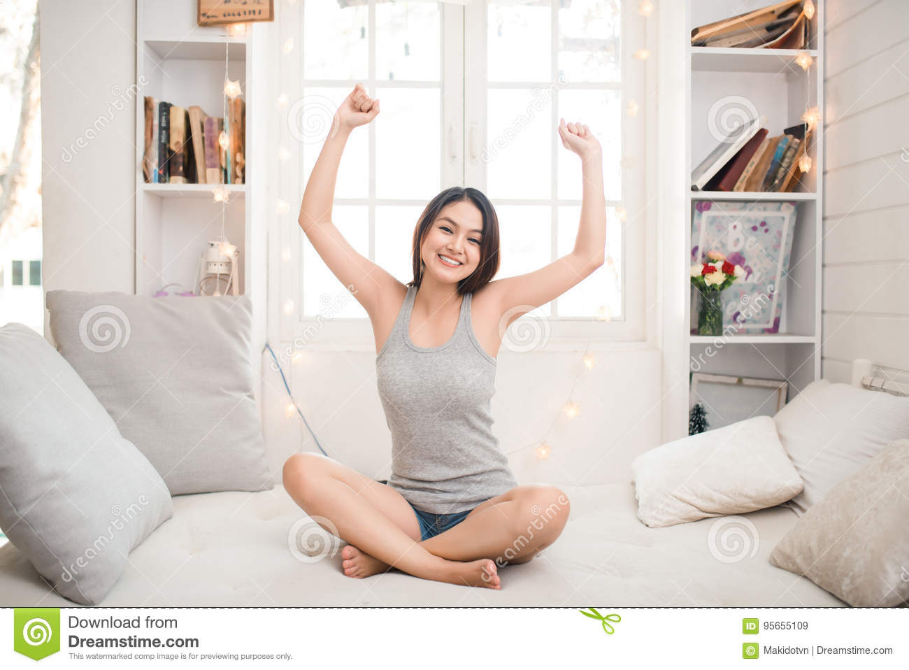 Woman stretching in bed after waking up, back view, entering a day happy and relaxed after good night sleep. Sweet dreams, good mo