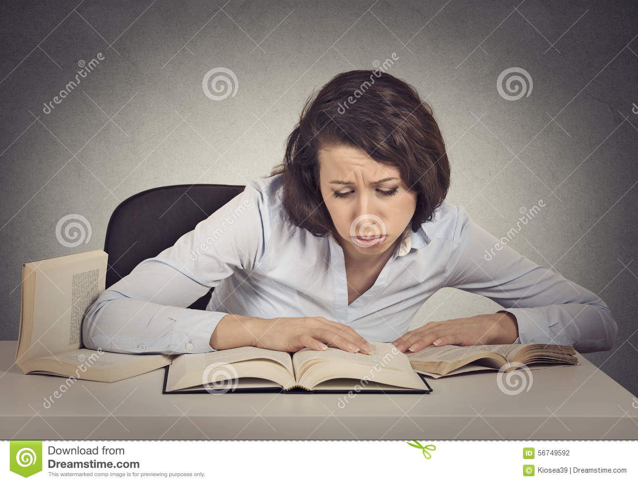 Woman student with desperate expression looking at her books