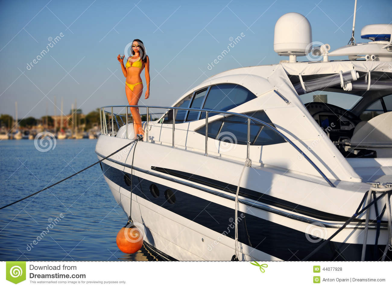 Woman in stylish bikini standing on the deck of motorboat.