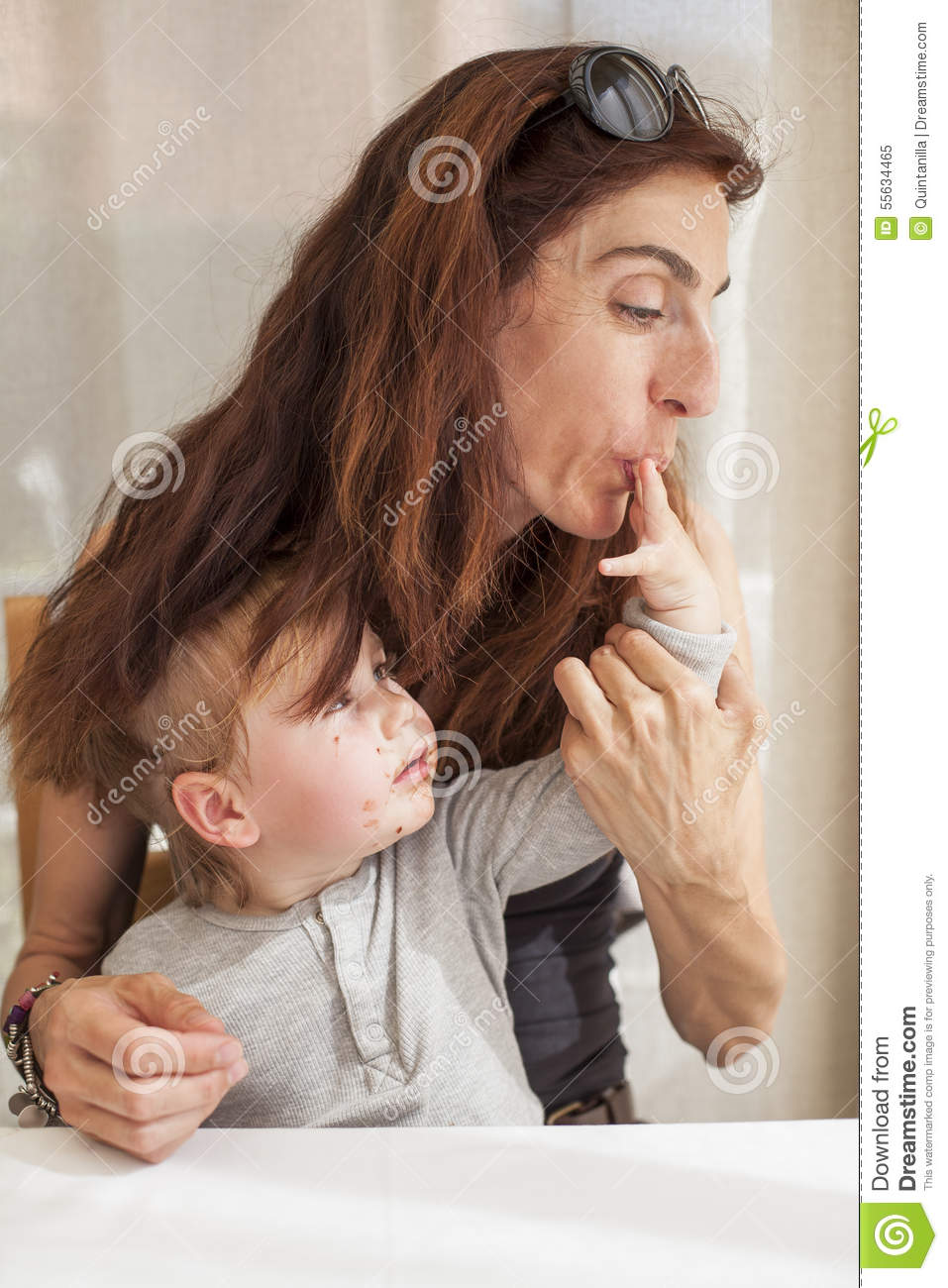 Brunette women mother with sunglasses on head sucking finger of her blonde  baby two years old age with grey shirt and chocolate smeared face sitting  in ...