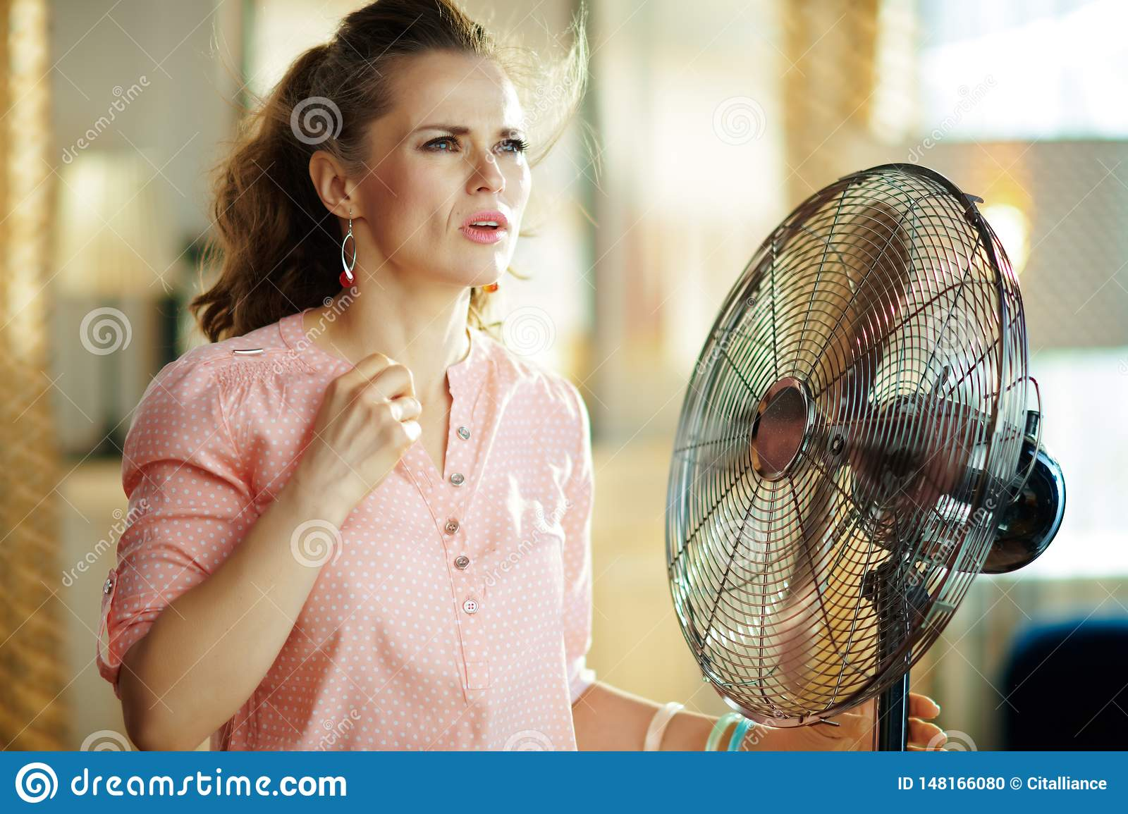 Woman suffering from summer heat while standing in front of fan