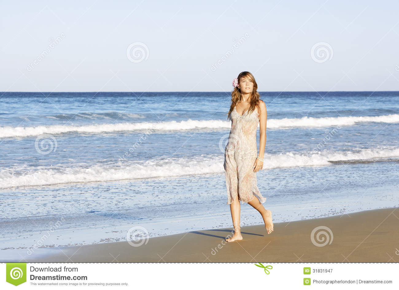 Woman walking on a beach royalty - Woman In Summer Dress Walking Across Beach Royalty Free Stock Photo