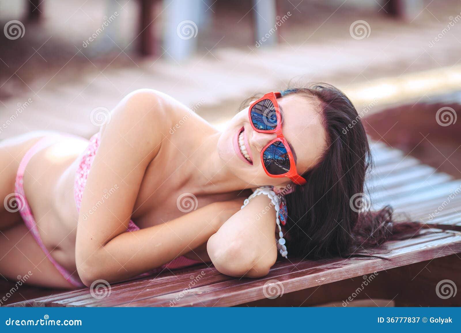 Woman sunbathing in bikini at tropical travel resort. Beautiful young woman lying on sun lounger near pool.