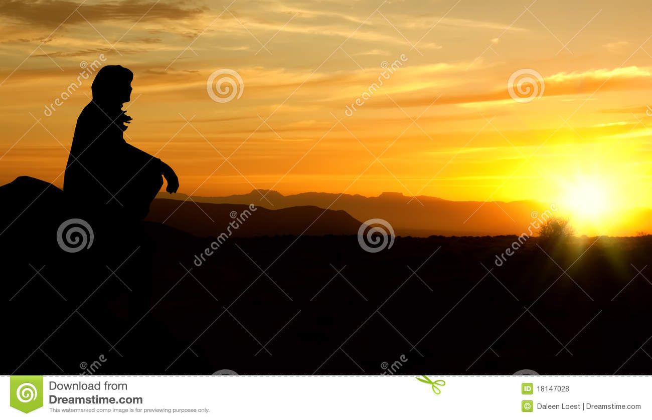 Single adult woman silhouette on rock watching yellow and orange ...