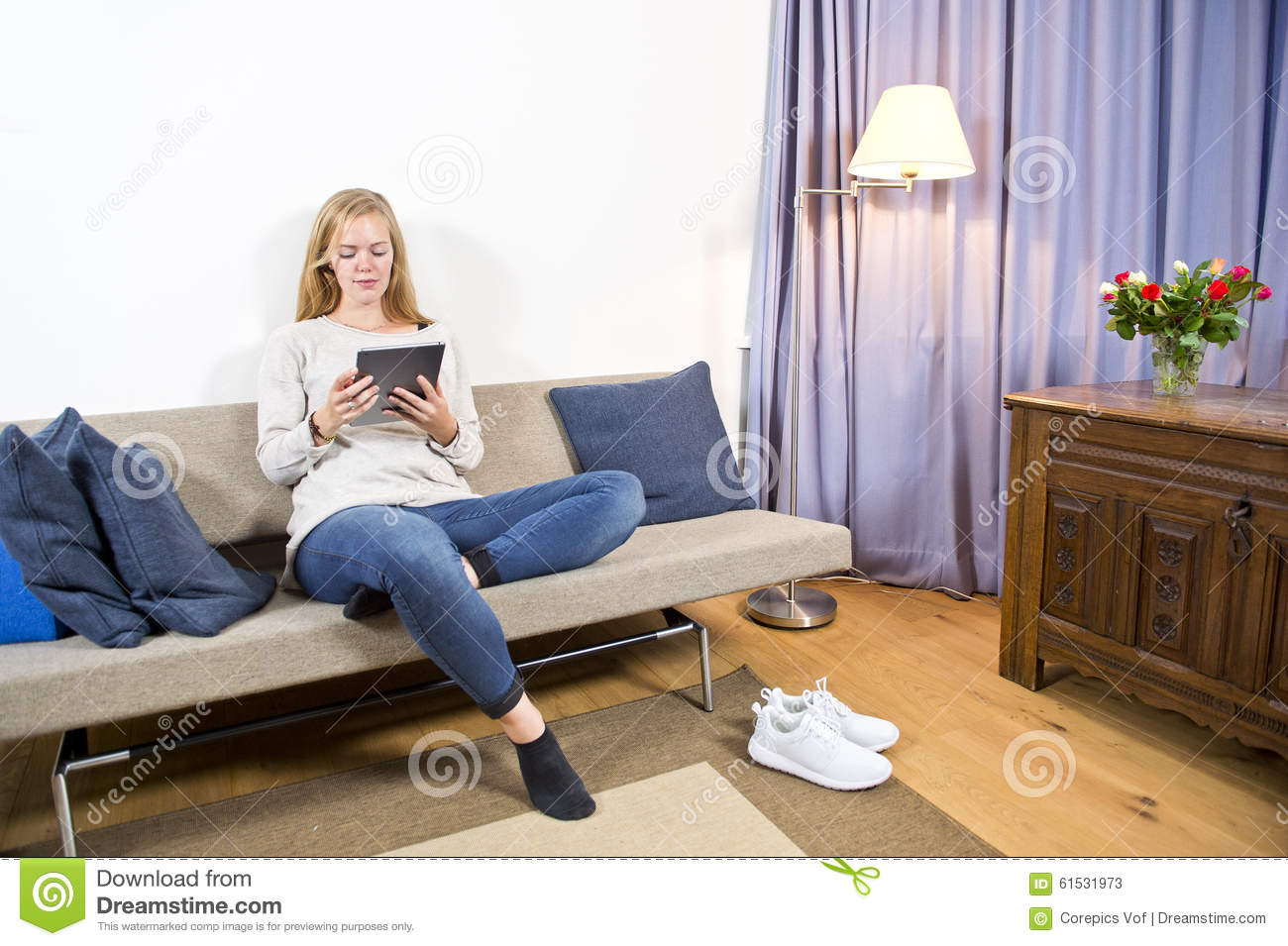 Woman surfing on a tablet in a living room stock image for Young modern living room
