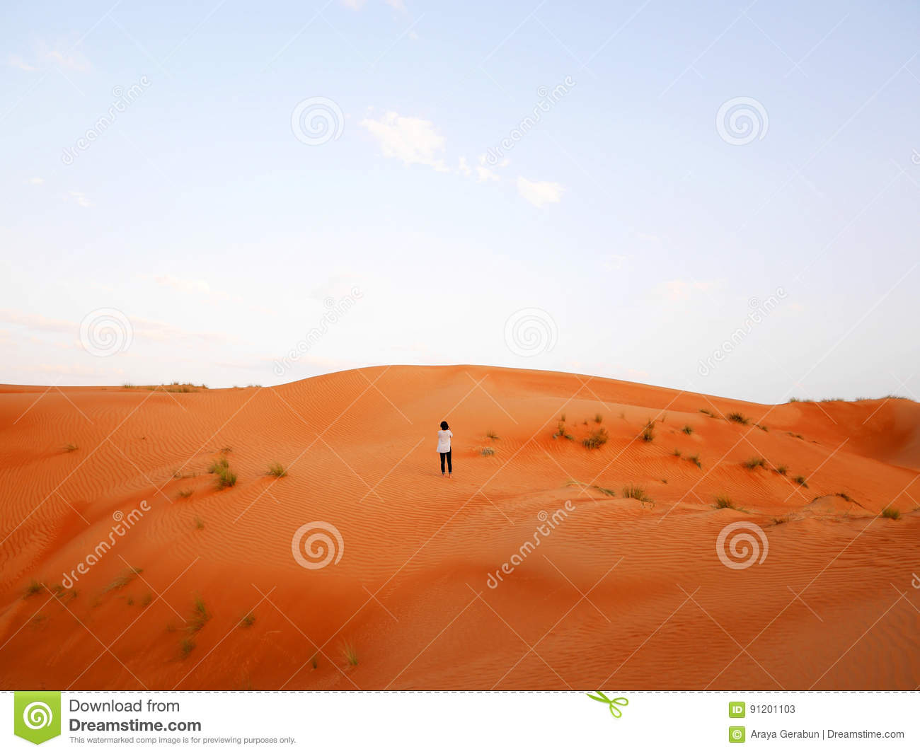 Woman surrounded by large sand dunes of Wahiba desert, Oman
