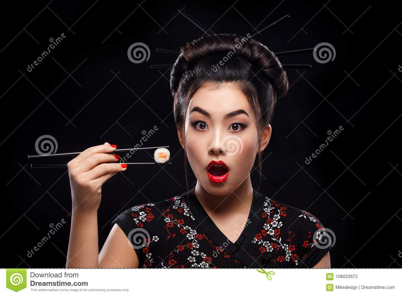 Surprised Asian woman eating sushi and rolls on a black background.