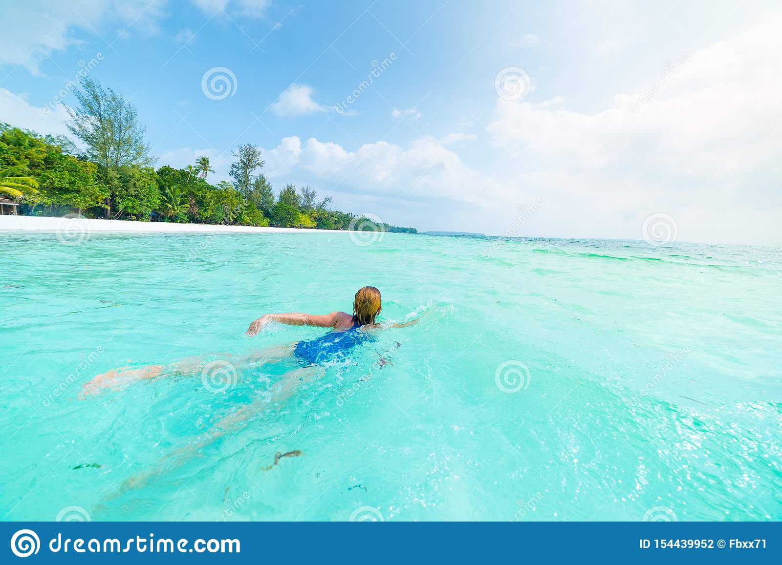Woman swimming in caribbean sea turquoise transparent water. Tropical beach in the Kei Islands Moluccas, summer tourist