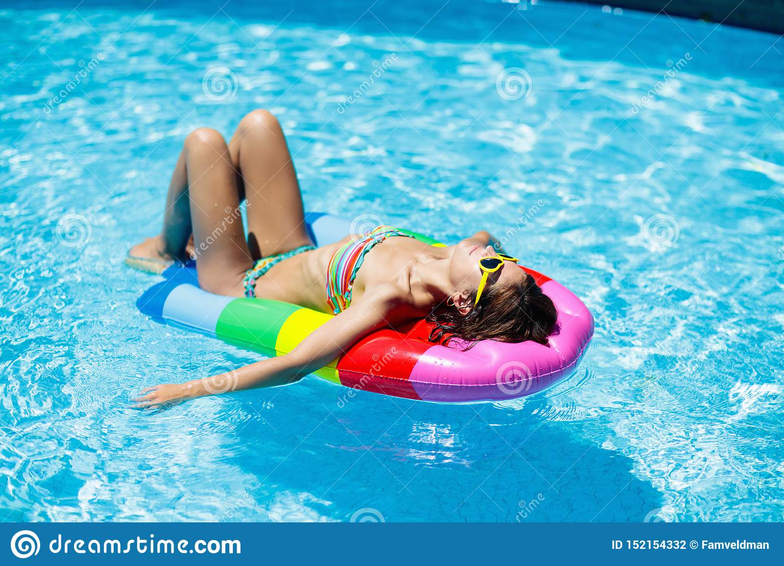 Woman in swimming pool on float. Female swimming