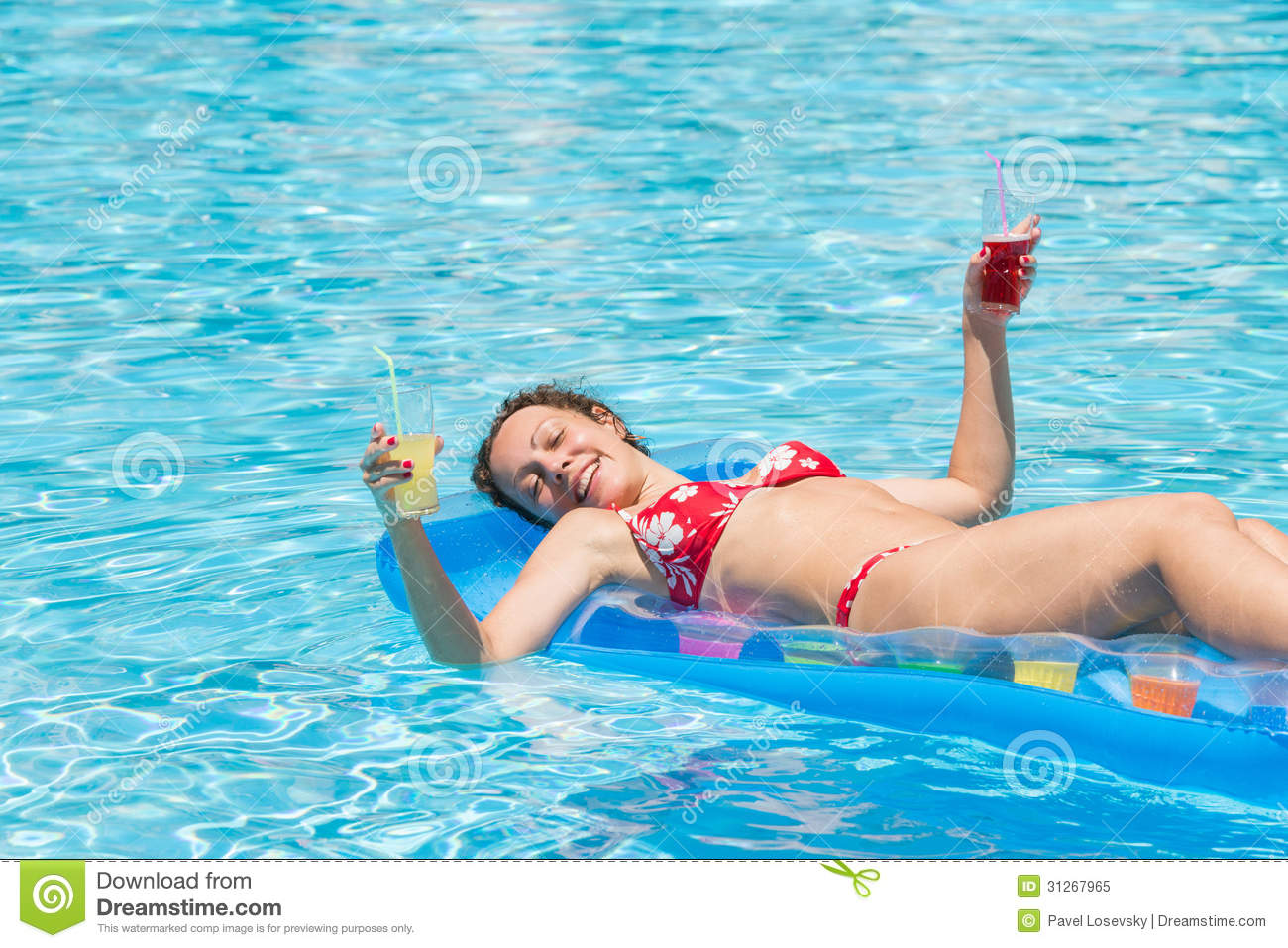 Woman Swimming In The Pool On An Inflatable Mattress
