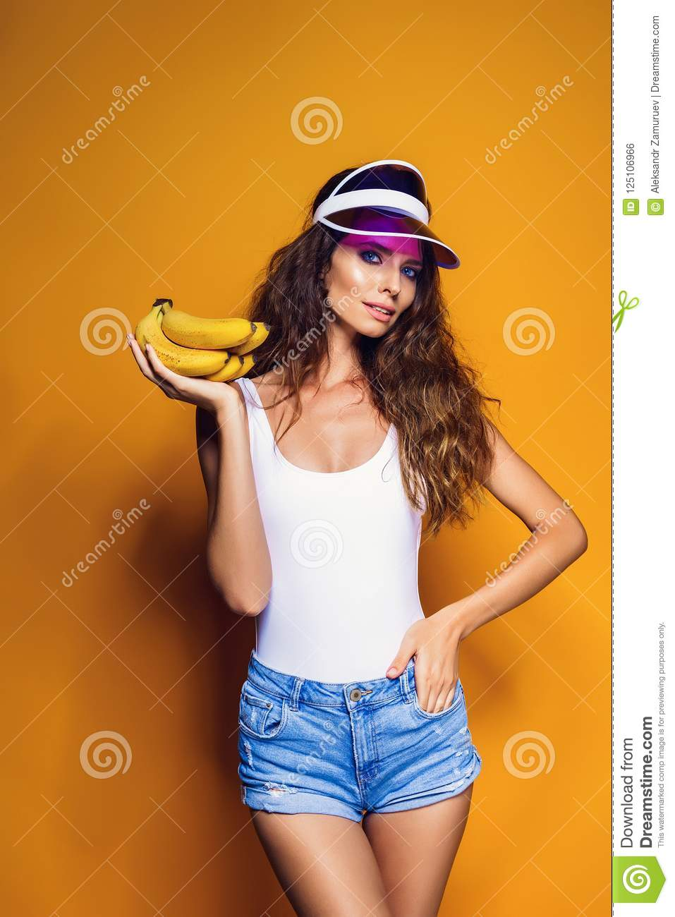 3fc3a52e13bc6 Woman in swimsuit and blue shorts holding banana and posing isolated over  yellow background