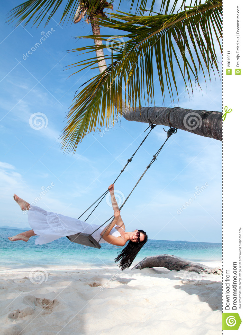 Woman on the swing on the beach in white dress