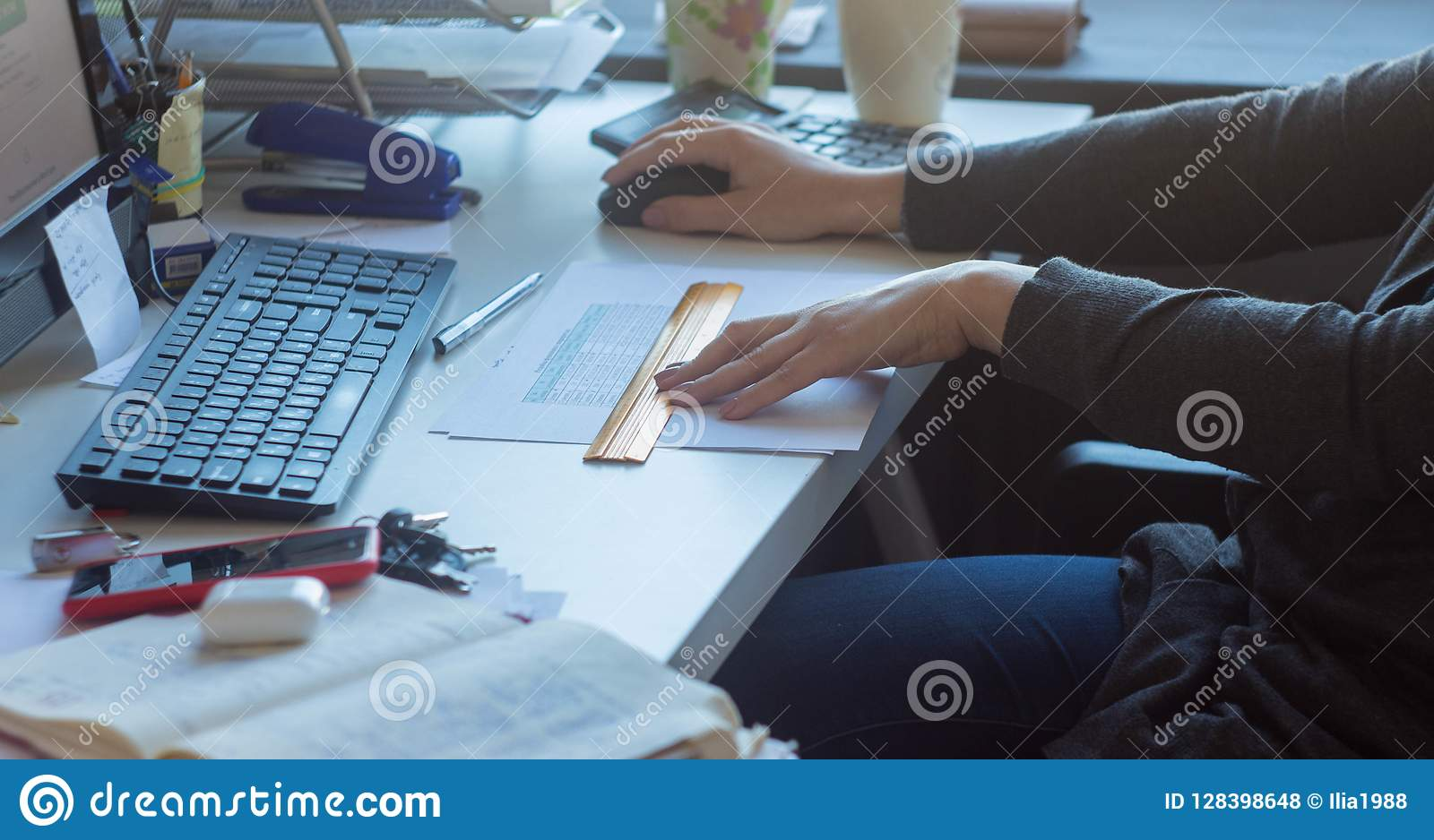 A woman at the table working at the computer