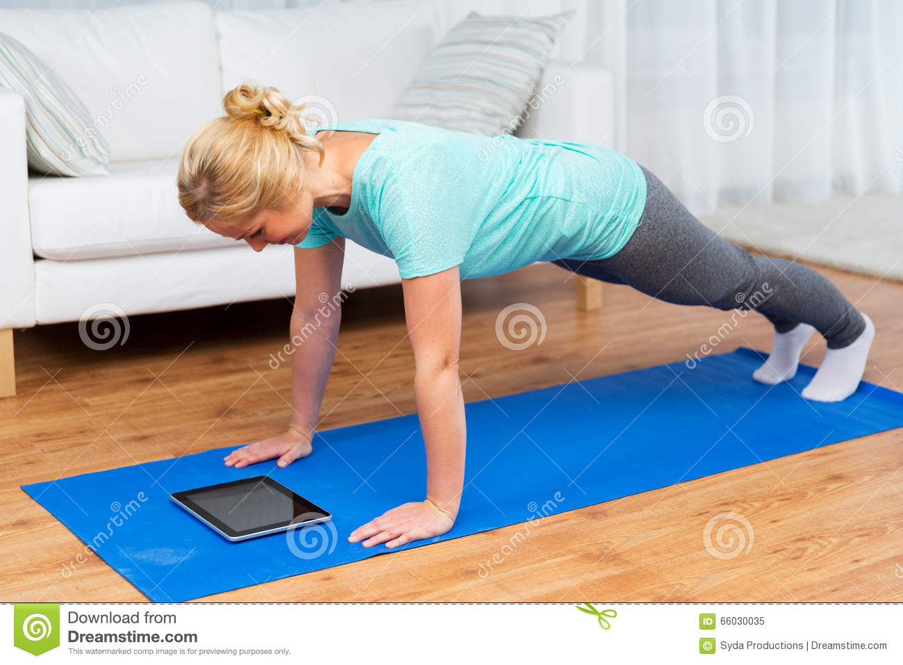 Woman with tablet pc doing plank exercise at home