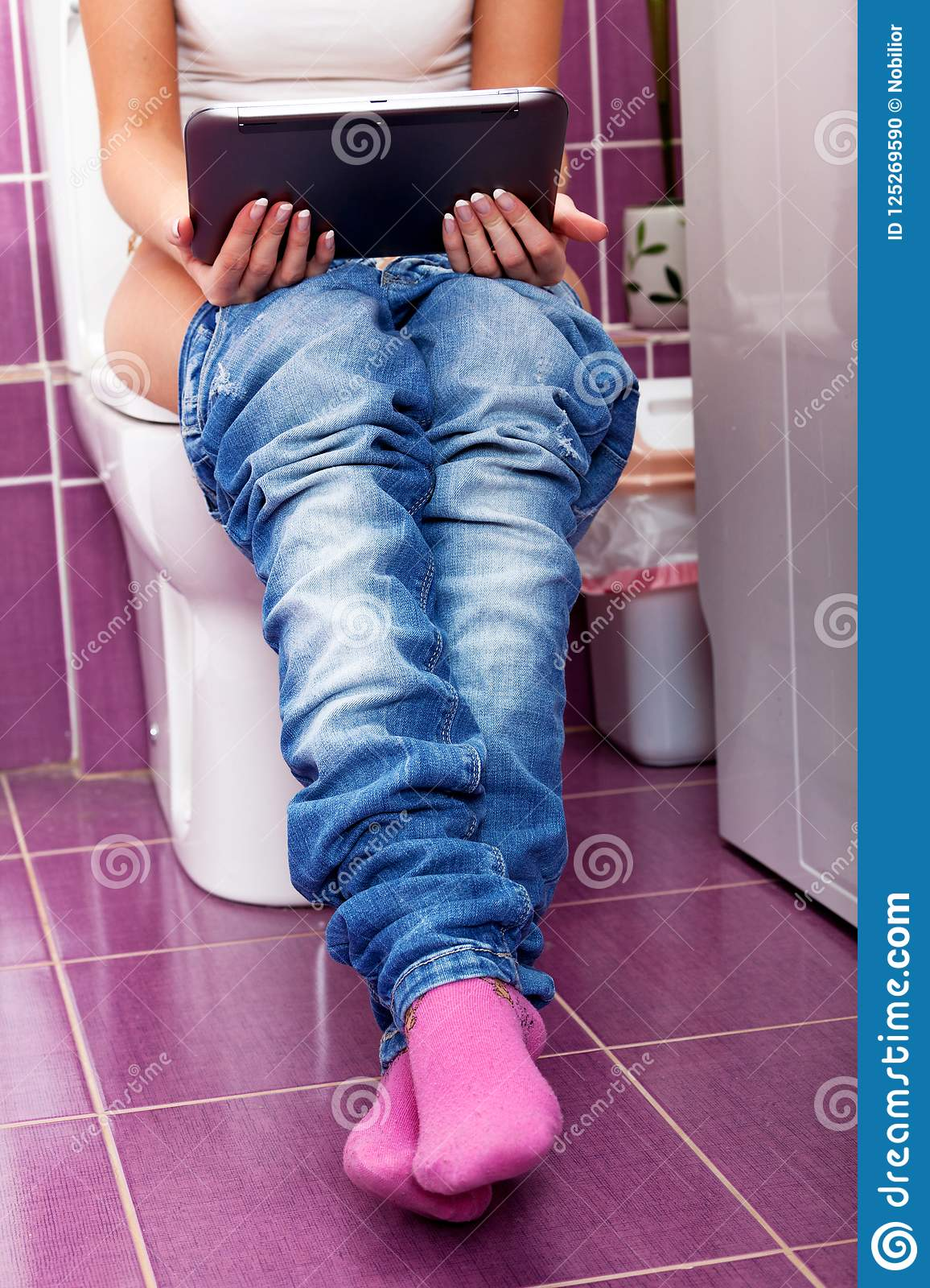 Selective Of Young Woman Sitting In The Toilet Working