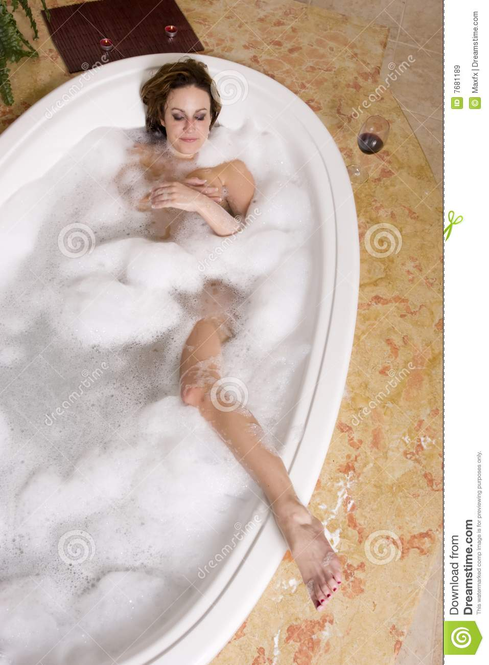 Cute girl in bubble bath. Portrait of cute young blond haired girl sat in bath with soap or foam bubbles on head royalty free stock images