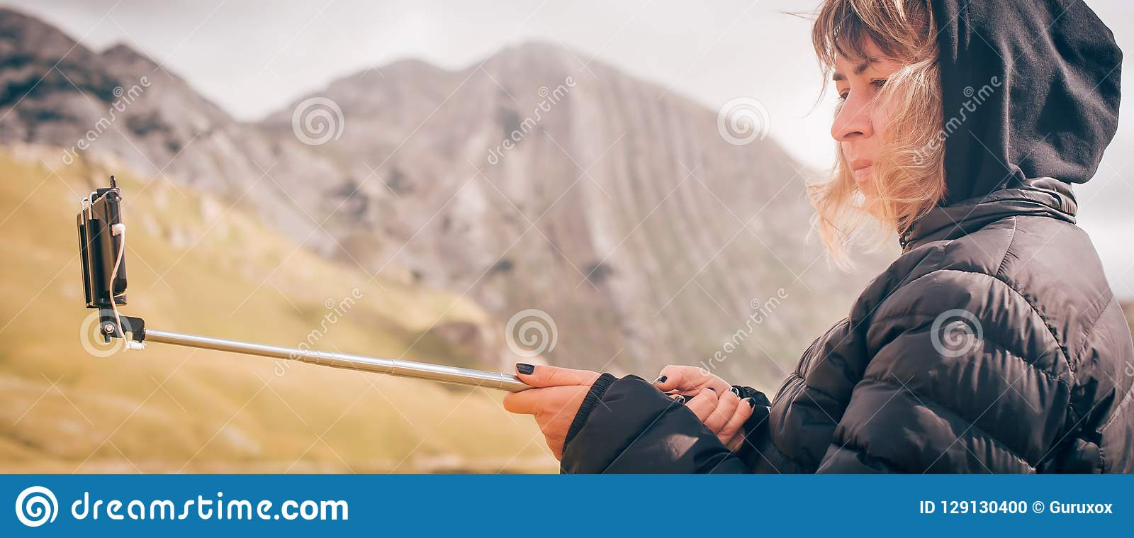 Woman taking panoramic picture of mountain landscape. Selfie photo stick