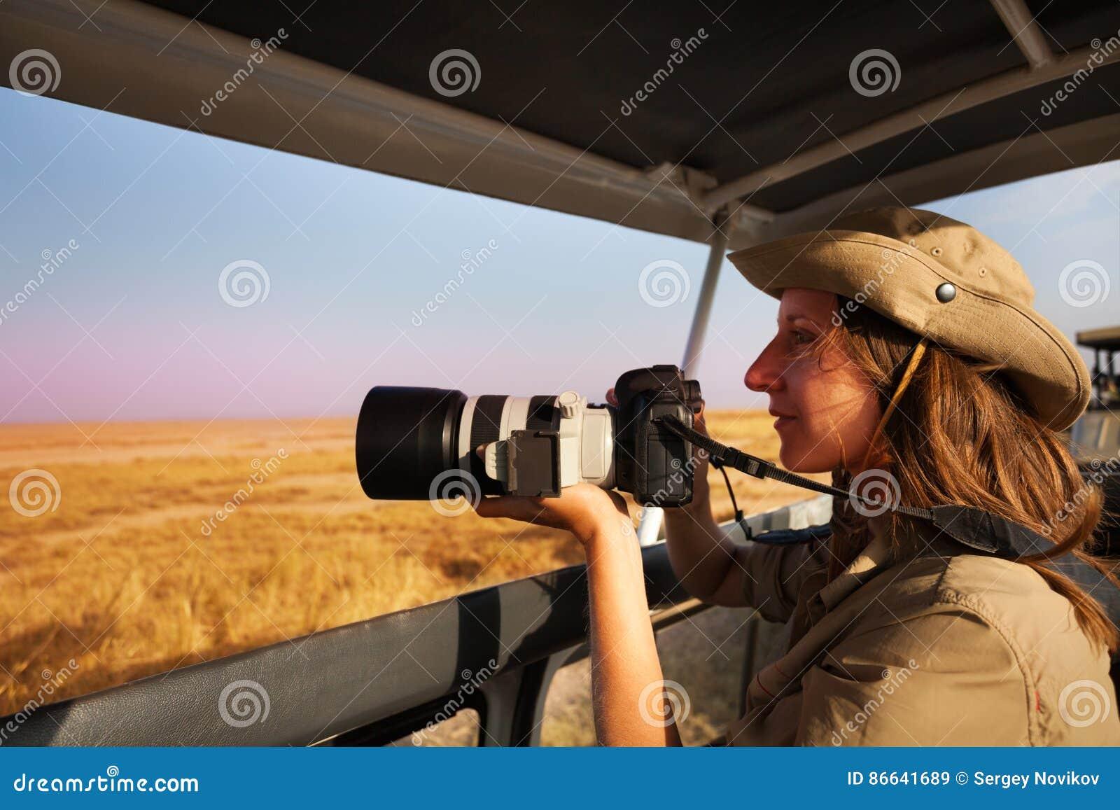 Woman Taking Photo Aboard Safari Jeep At Savannah Stock