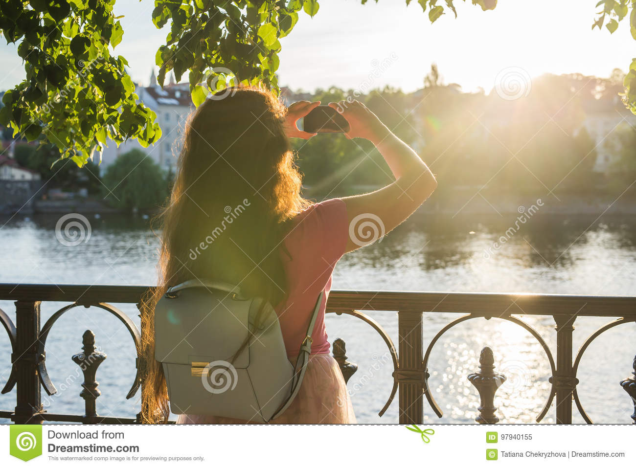 Woman taking pictures with smartphone. Stylish summer traveler woman in hat with camera outdoors in european city, Czech