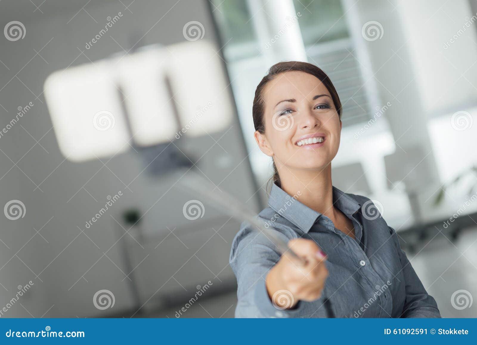 woman taking a self portrait using a selfie stick stock photo image 61092591. Black Bedroom Furniture Sets. Home Design Ideas