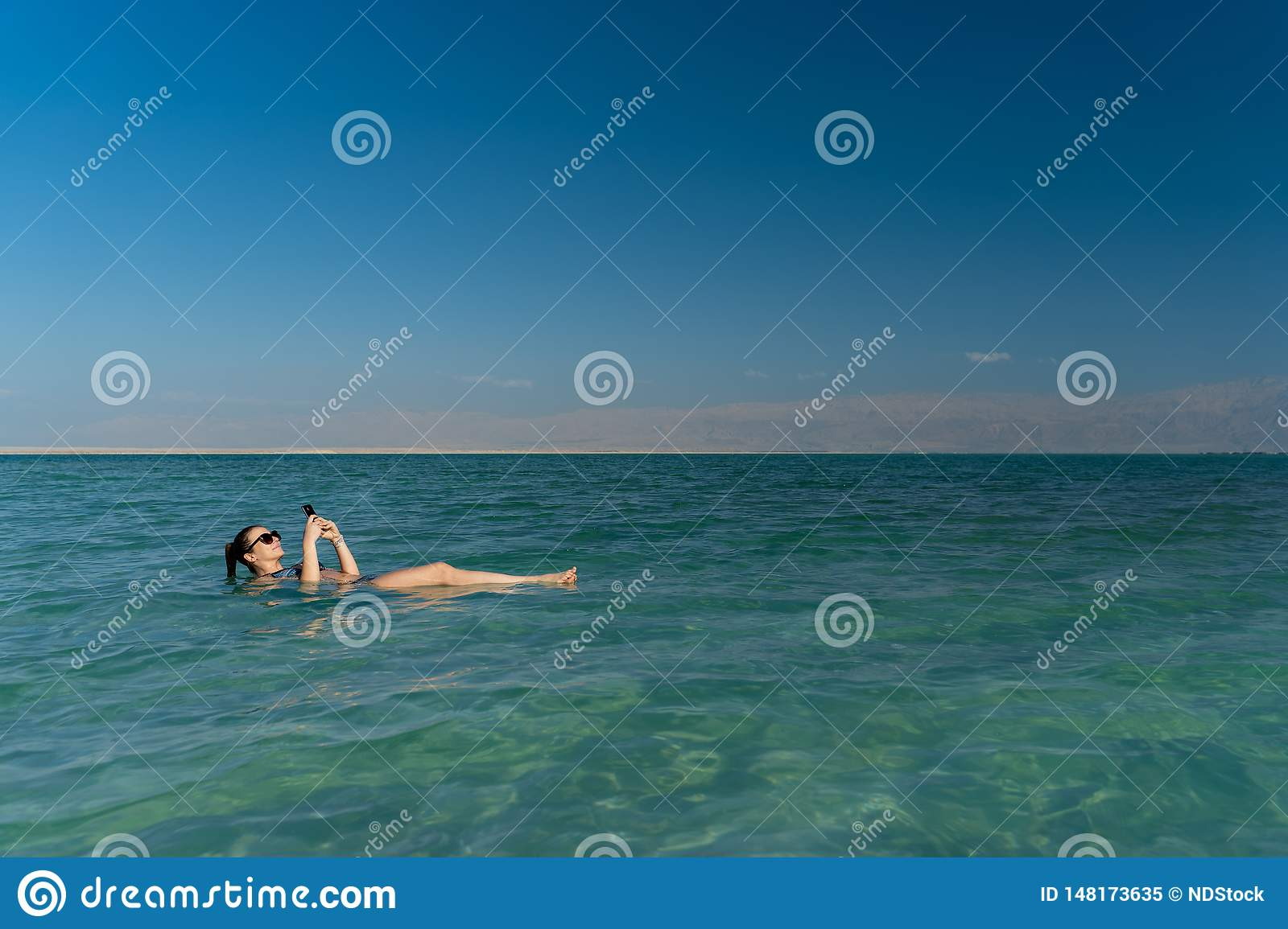 Young woman floating on the water surface of the dead sea and using her smartphone