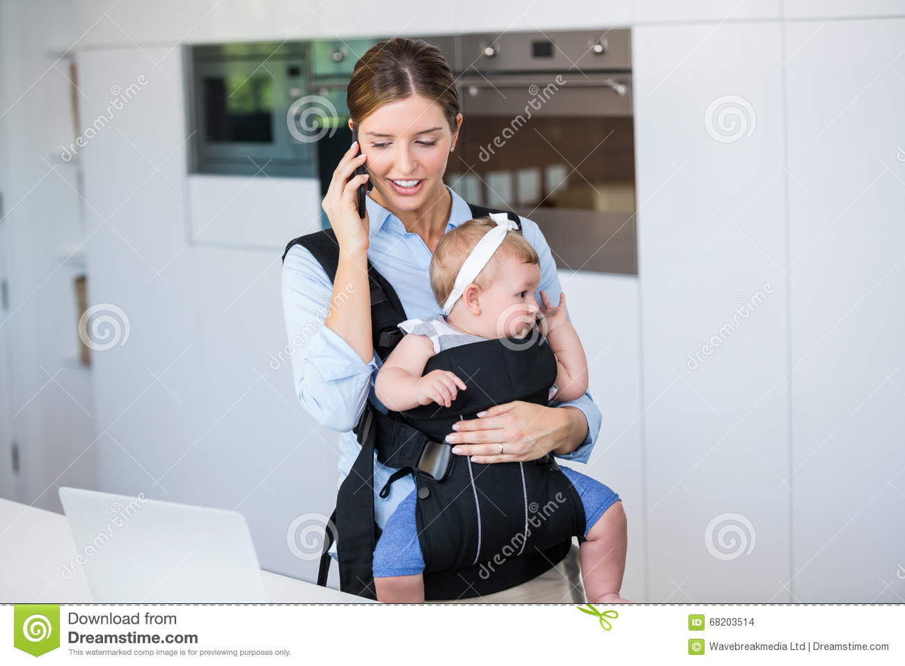 Woman talking on mobile phone while carrying baby girl