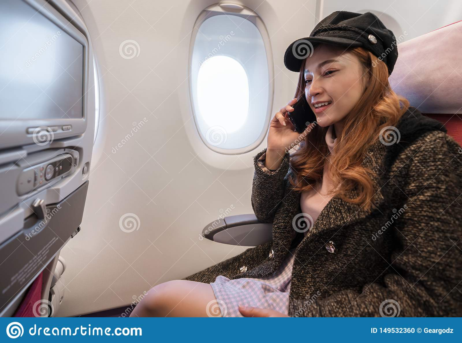 Woman talking with smartphone in airplane in flight time