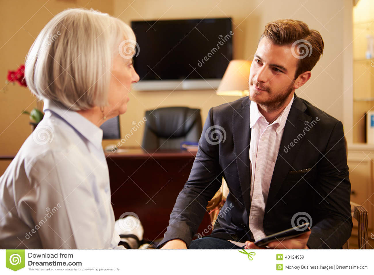 Woman Talking To Male Counsellor Using Digital Tab