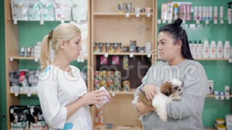 Woman talking to a saleswoman in a vet store for pets, buying pills and  food for sick dog