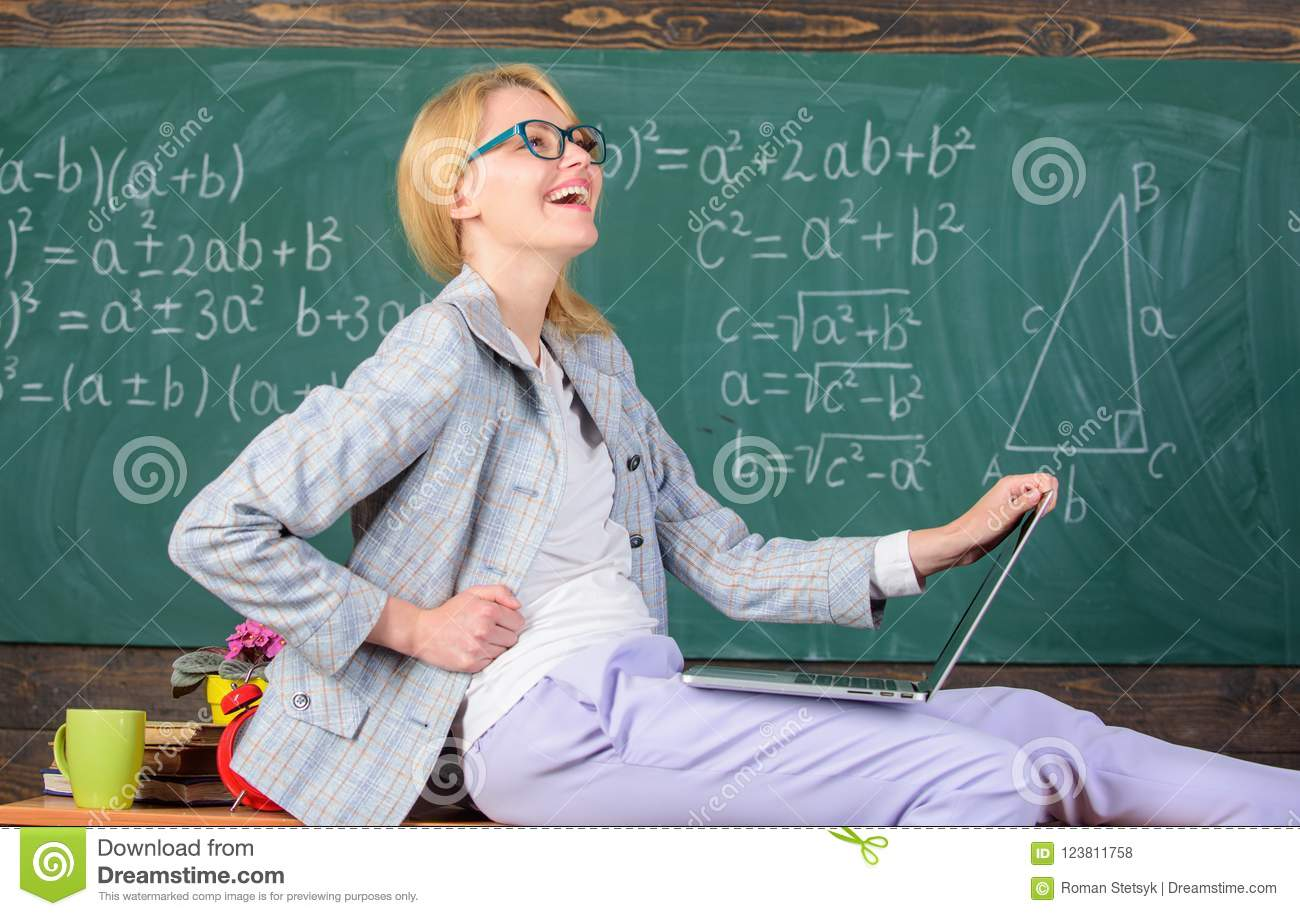 woman teacher hold laptop sit table classroom chalkboard background