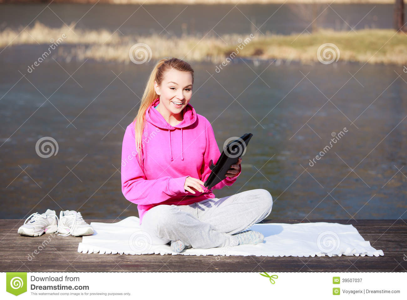 Woman teenage girl in tracksuit using tablet on pier outdoor
