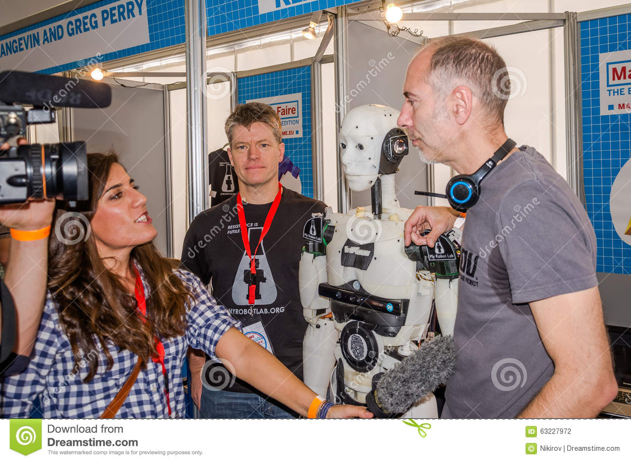 A woman television journalist interviews with the microphone at the engineer developer robot drone who stands beside his developme