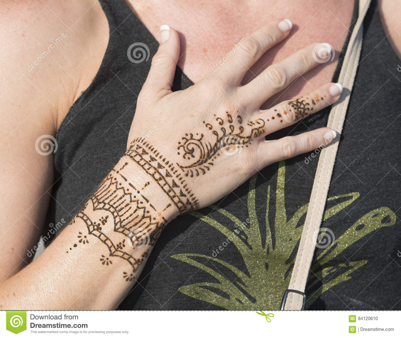 31ff97ef4 A woman wearing a tank top has a temporary Henna design painted on her hand  at Venice Beach, California. Her right hand is extended and placed across  her ...