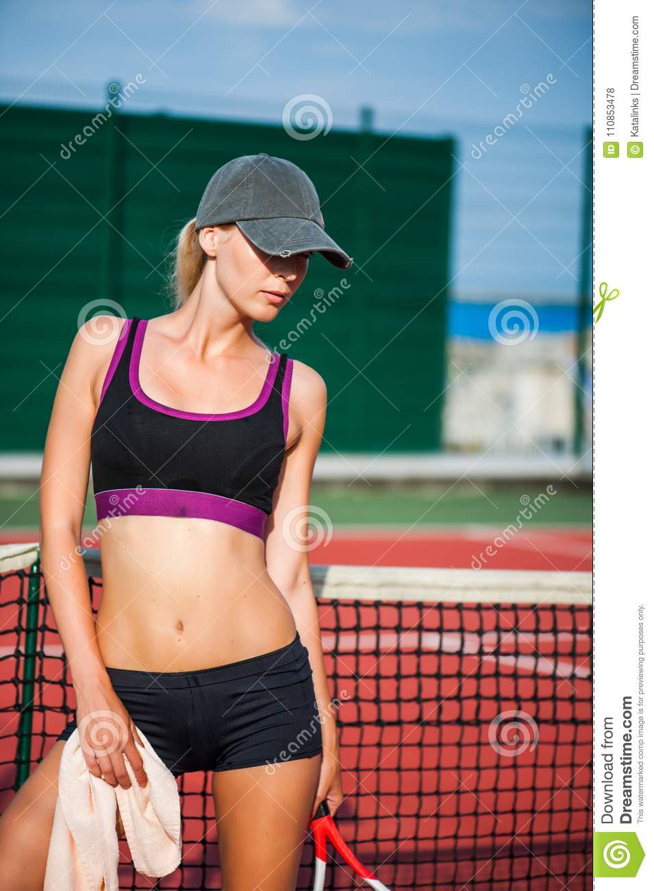 4cc834b9e11a4 Young beautiful Woman tennis player wearing cap having rest while standing  on tennis court after match. Wipe the sweat with a towel