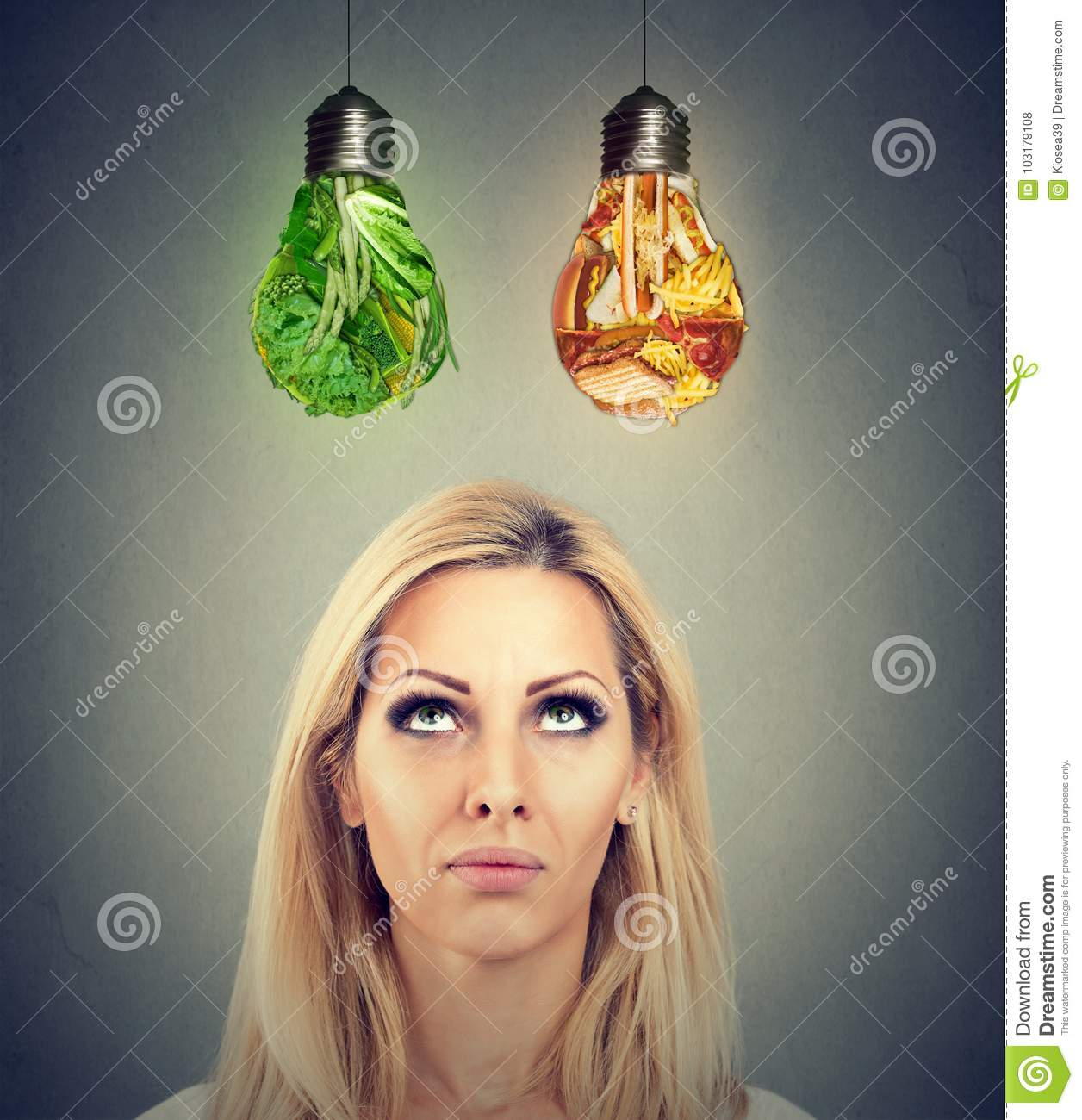 Woman thinking making a diet choice looking up at junk food and green vegetables shaped as light bulb