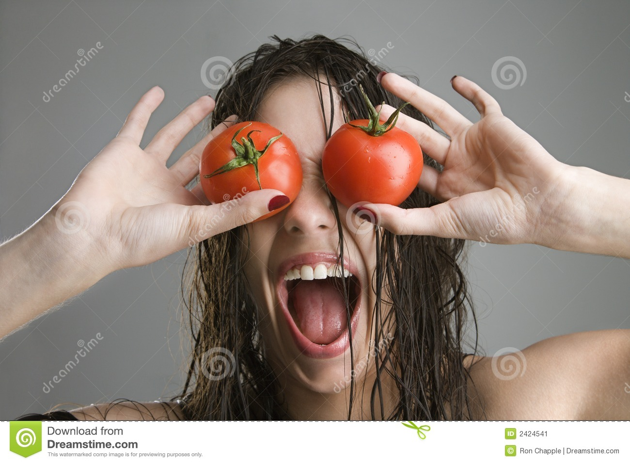Woman with tomatoes over eyes.