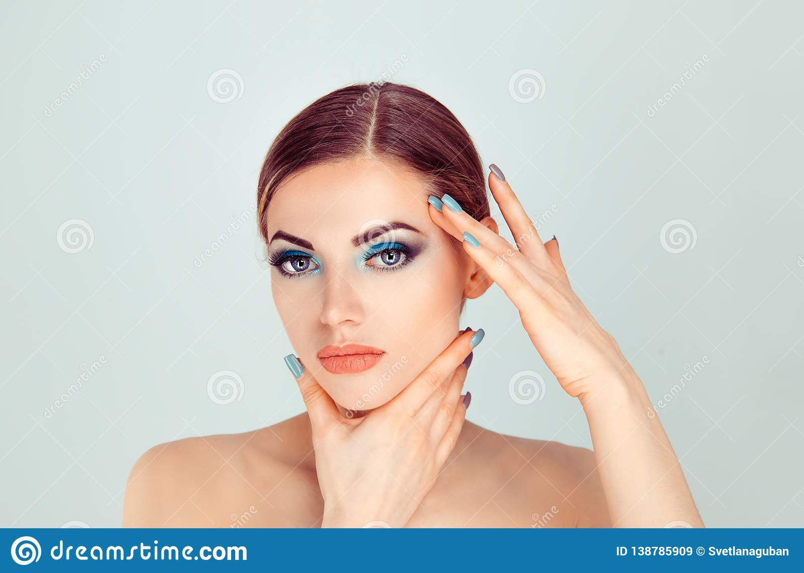 Woman touching face with hands showing perfect makeup and soft skin