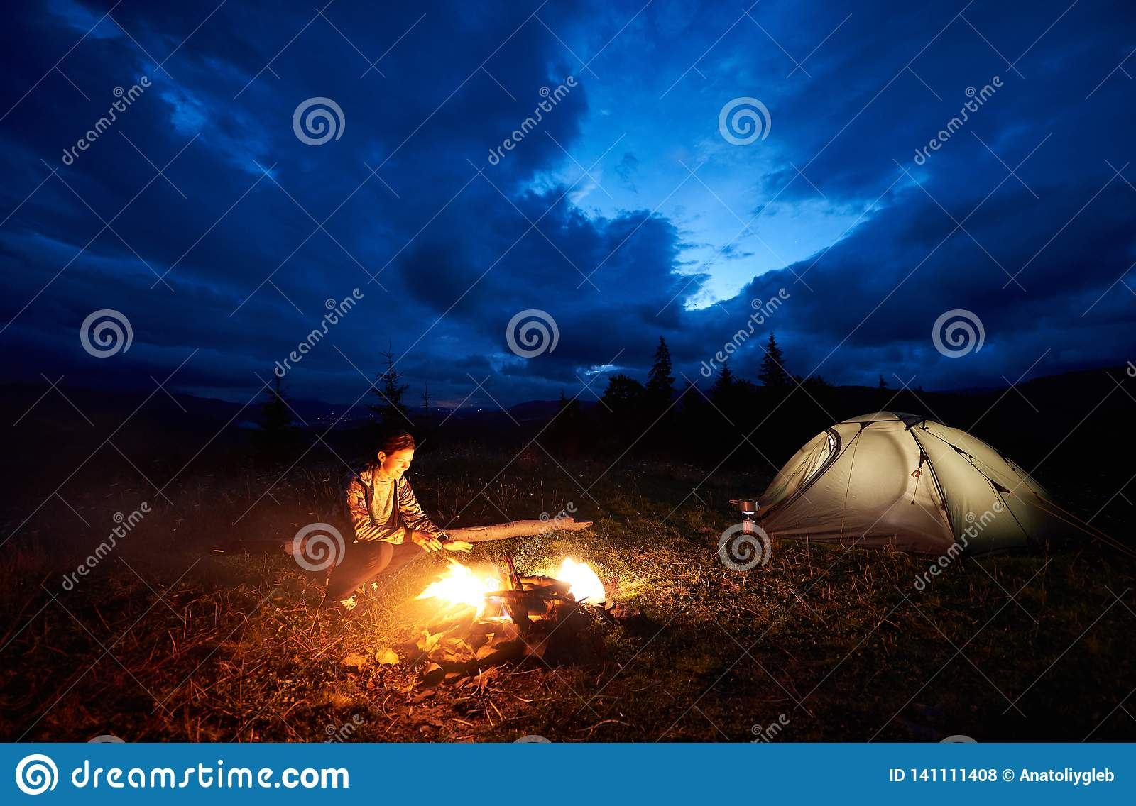 Woman tourist resting at night camping in mountains near campfire and tent under evening cloudy sky