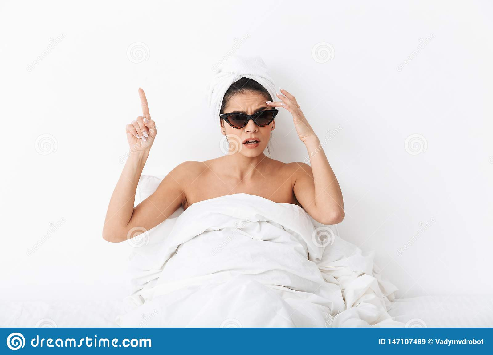 Woman with towel on head lies in bed covering body under blanket isolated over white wall background wearing sunglasses pointing