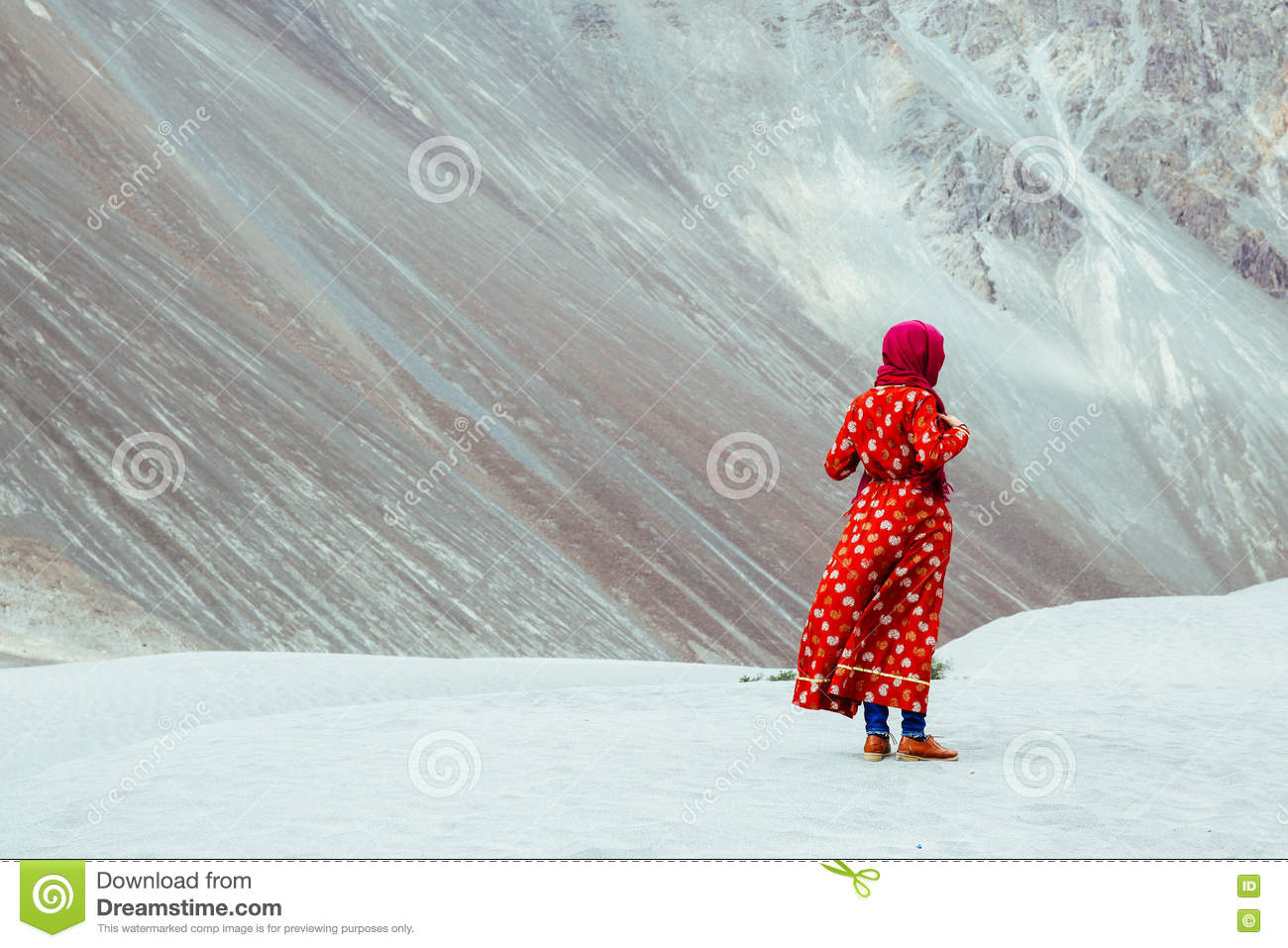 Woman in traditional Indian dress standing in desert in Ladakh, India
