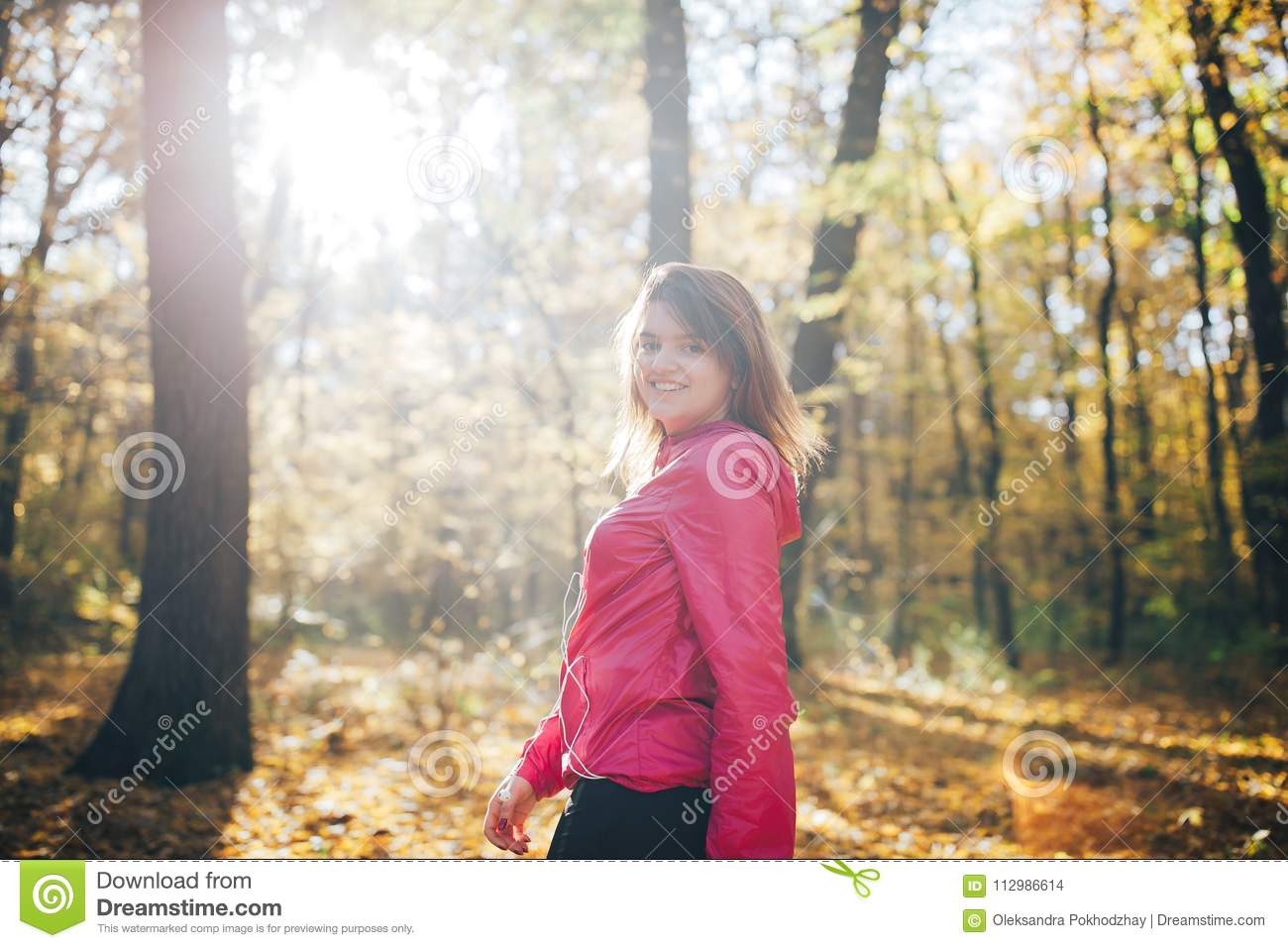 Woman trains in the morning autumn forest. Good morning light.