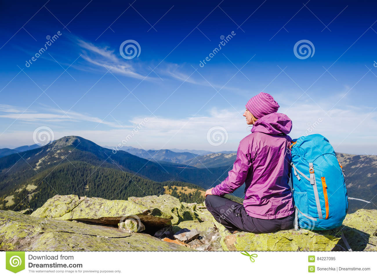 Woman Traveler with Backpack hiking in the Mountains and beautiful summer landscape