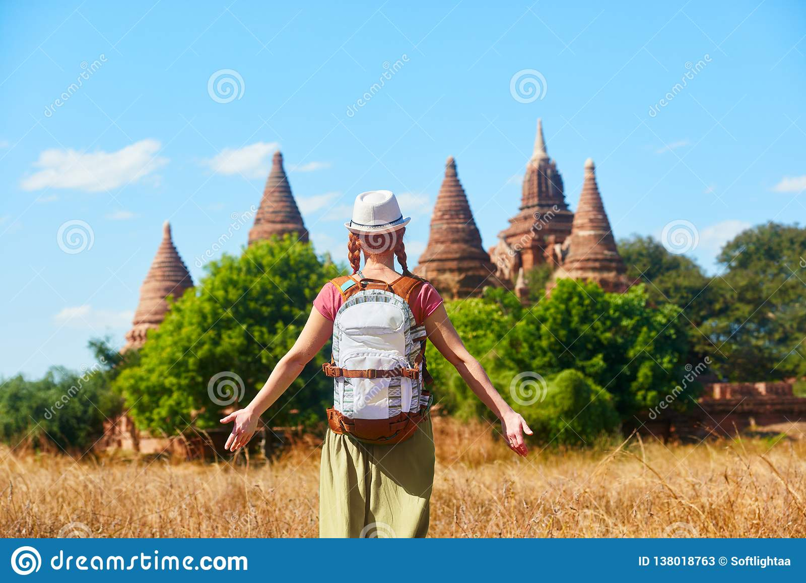 Woman traveler with a backpack walking through field to ancient stupas