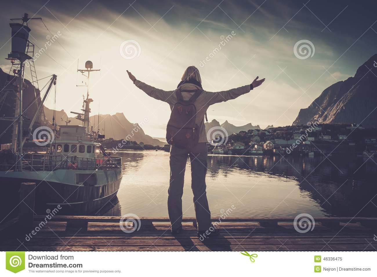Woman traveler in Reine village with arms wide open